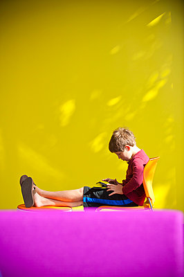 Caucasian boy relaxing and reading digital tablet - p555m1532501 by Stephen Simpson Inc