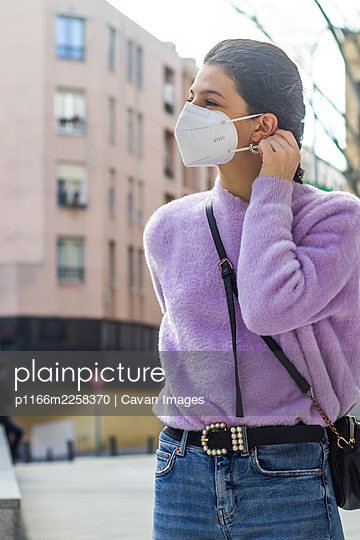 young woman with KN95 protective mask on the street - p1166m2258370 by Cavan Images