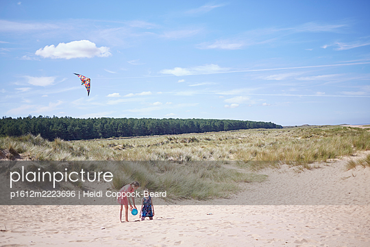 Two young girls playing on beach  - p1612m2223696 by Heidi Coppock-Beard