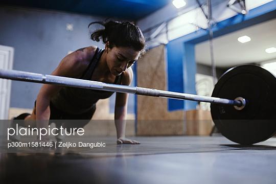 Woman doing push ups at barbell in gym - p300m1581446 von Zeljko Dangubic