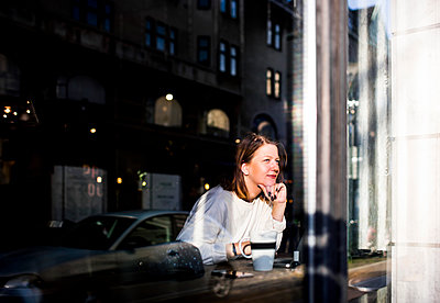 Smiling woman looking through window while sitting in cafe - p1264m1122005f by Astrakan