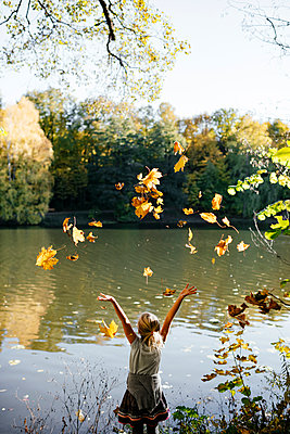 Back view of little girl standing at riverside throwing autumn leaves in the air - p300m2140313 by Ekaterina Yakunina