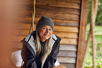 Smiling mature woman wearing knit hat in back yard - p300m2241310 by Maya Claussen