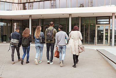 Rear view of multi-ethnic students walking against building in high school campus - p426m2072228 by Kentaroo Tryman