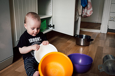 Baby boy creates choas in kitchen after clearing out kitchen cupboard - p795m2161099 by JanJasperKlein
