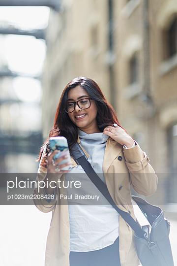 Smiling businesswoman using smart phone on street - p1023m2208428 by Paul Bradbury