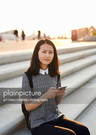 Asiatin sitzt mit Smartphone auf Treppe - p1124m1169898 von Willing-Holtz
