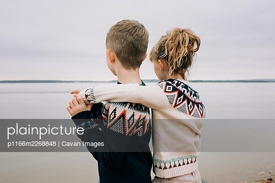 brother and sister hugging looking out to sea on a cloudy day together - p1166m2268848 by Cavan Images