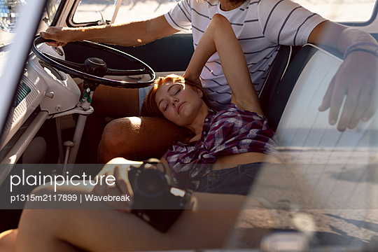 Beautiful woman relaxing on man lap in front seat of camper van at beach - p1315m2117899 by Wavebreak