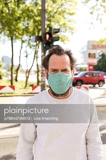 Man with face mask crossing a street - p788m2184012 by Lisa Krechting