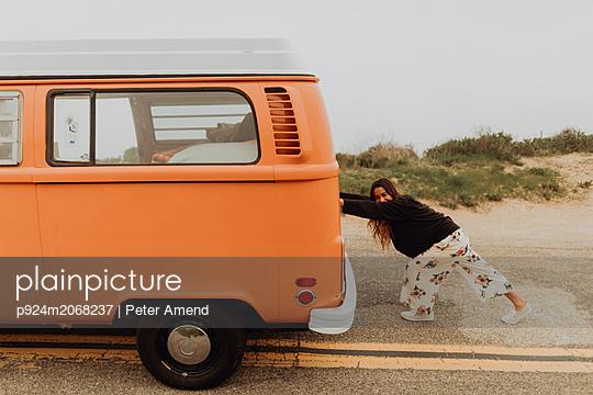 Young woman pushing recreational vehicle at coastal roadside, Jalama, California, USA - p924m2068237 by Peter Amend