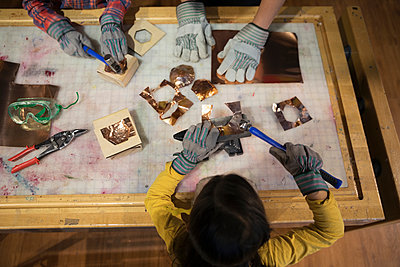 Overhead view girl hammering metal in science center workshop - p1192m1194212 by Hero Images