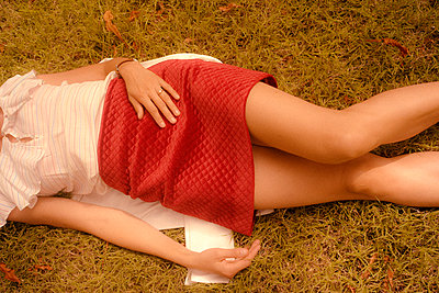 Youg woman lying on the grass in a park - p1654m2253711 by Alexis Bastin