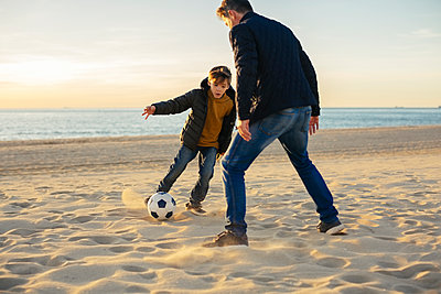 Father and son playing football on the beach - p300m1562560 by Bonninstudio