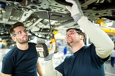 Two colleagues working at car underbody in modern factory - p300m2144862 by Fotoagentur WESTEND61