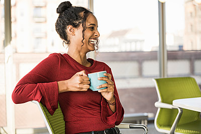 Happy young businesswoman having a coffee break in office - p300m2160316 by Uwe Umstätter