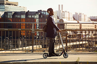 Side view of young man riding electric push scooter on bridge in city - p426m2075395 by Maskot