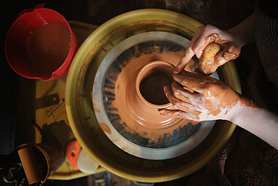 Hands of Caucasian woman shaping pottery clay on wheel - p555m1481945 by JGI/Jamie Grill