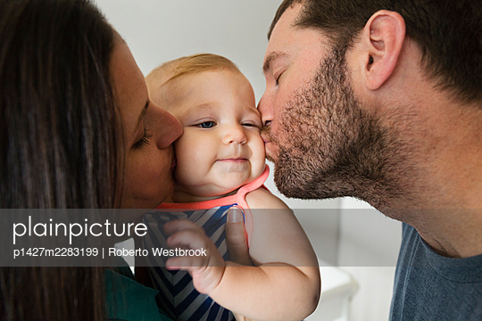 Close up of mid adult couple kissing baby daughter on each cheek - p1427m2283199 by Roberto Westbrook