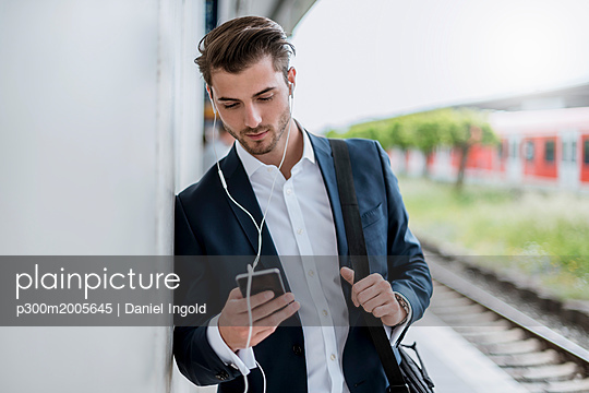 Businessman at the station with earbuds and cell phone - p300m2005645 von Daniel Ingold
