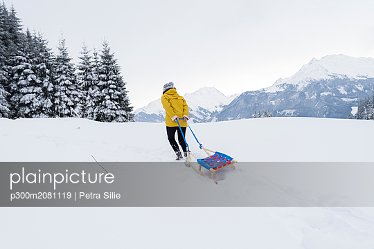 Austria, Tyrol, Thurn, back view of woman pulling sledge in snow-covered landscape - p300m2081119 by Petra Silie