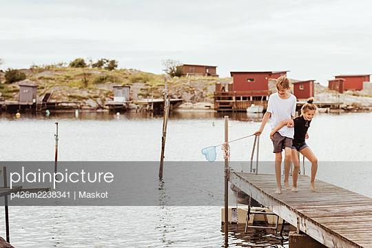 Siblings with fishing net walking on jetty at marina during vacation - p426m2238341 by Maskot