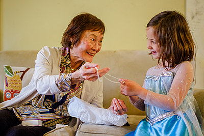 A smiling girl in princess costume opens up gift from her grandmother - p1166m2157363 by Cavan Images