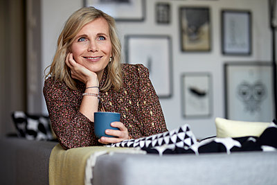 Smiling blond woman relaxing at home sitting on couch - p300m2167466 by Rainer Berg