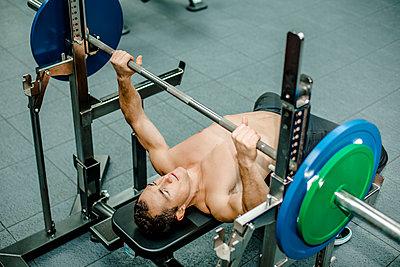 Shirtless athlete doing weightlifiting at bench press in gym - p300m2267006 by Katja Velmans