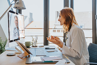 Healthcare worker talking to coworker on video call over computer while sitting at office - p300m2267729 by Mareen Fischinger