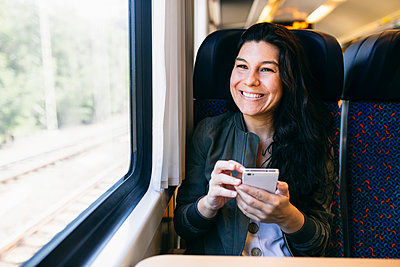 Woman with mobile phone looking through window while sitting in train - p300m2281315 by Andrés Benitez