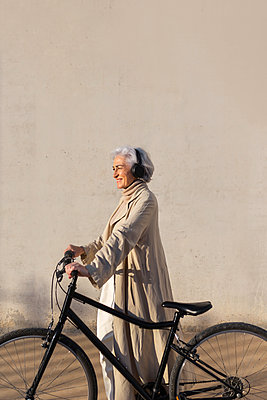 Smiling woman looking away while standing with bicycle - p300m2281470 by PICUA ESTUDIO