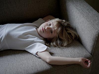 Blonde girl lying on sofa - p945m1446195 by aurelia frey