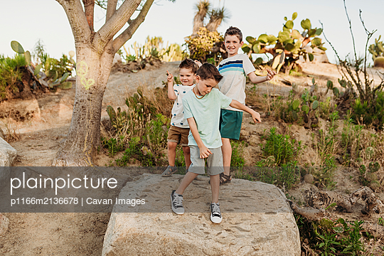 Three young brothers dancing on rock in sunny California cactus garden - p1166m2136678 by Cavan Images