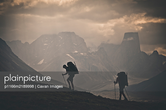 Silhouette of two backpackers hiking with rugged mountain view. - p1166m2189998 by Cavan Images