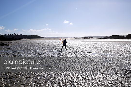 Boy crossing beach at low tide - p1307m2257658 by Agnès Deschamps