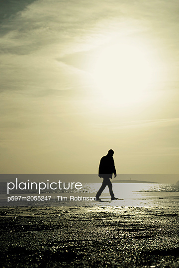 Silhouette man walking on beach with low sun - p597m2055247 by Tim Robinson