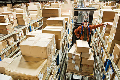 A Caucasian male warehouse worker standing on a motorized stock picker  and surrounded by products in boxes in a distribution warehouse. - p1100m2002270 by Mint Images