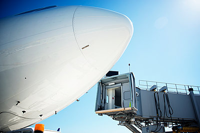 Low angle view of passenger boarding bridge and airplane against blue sky - p1166m1151339 by Cavan Images
