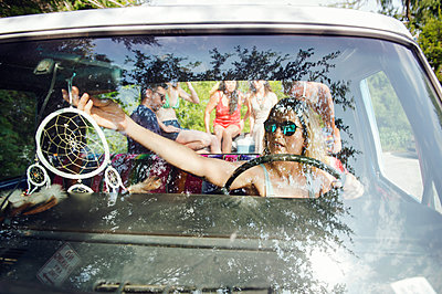 Woman adjusting rear-view mirror while friends sitting on pick-up truck - p1166m1174258 by Cavan Images