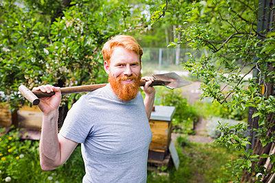 Portrait confident, smiling man with shovel in garden - p301m2075596 by Sven Hagolani