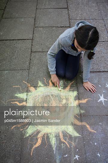 Mädchen malt Sonne mit Kreide - p045m1588903 von Jasmin Sander