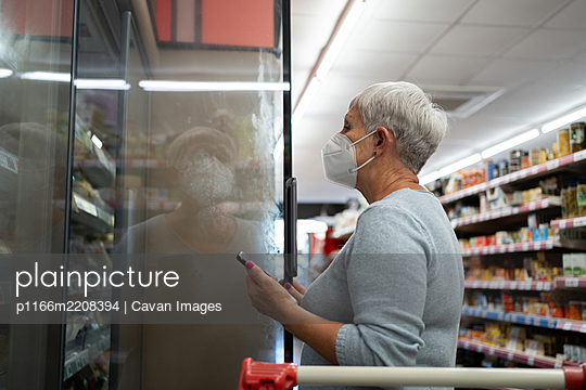 Caucasian elderly woman with white hair  shopping in supermarket - p1166m2208394 by Cavan Images