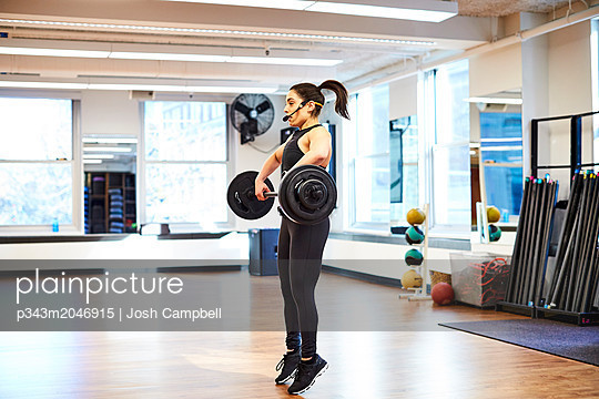 Fitness instructor lifting weights - p343m2046915 by Josh Campbell