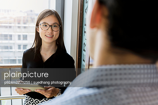 Germany, Bavaria, Munich, Female student talking to colleague in corridor - p924m2271255 by suedhang photography