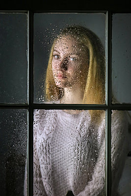 Female teenager behind wet window pane - p1019m2056887 by Stephen Carroll