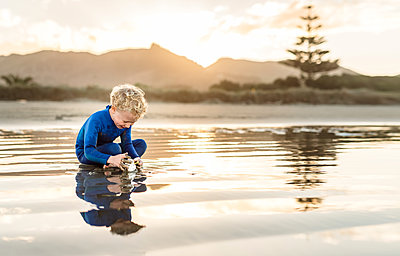 Happy preschooler playing at beach at dusk - p1166m2137633 by Cavan Images