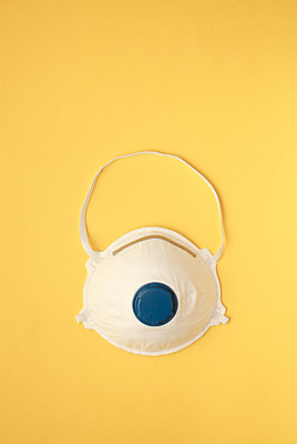 face mask or dust mask or filtering facepiece respirator - breathing protection against air pollution or flu or virus outbreak covid19 on yellow background - p1166m2174094 by Cavan Images