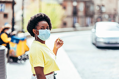 Portrait of black girl with face mask and afro hair waiting in an old city street. - p1166m2269360 by Cavan Images