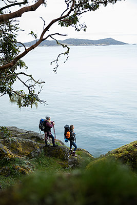 Mother and daughter backpacking on cliff overlooking ocean - p1192m2000375 by Hero Images